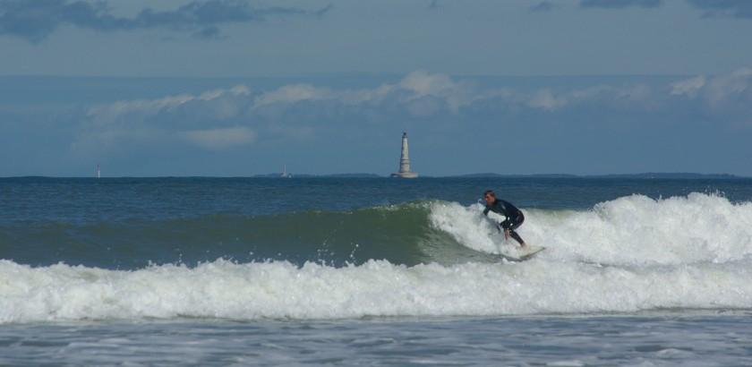 Wellenreiter mit Leuchtturm Plateau de Codouan im Hintergrund